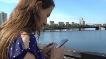mulher usando um smartphone perto do rio