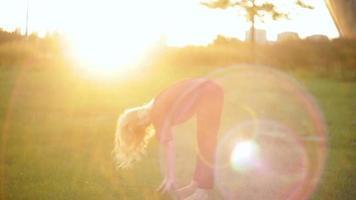 junge Frau, die Yoga auf Gras tut
