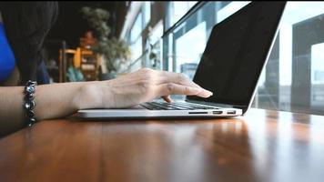 manos de mujer escribiendo en una computadora portátil