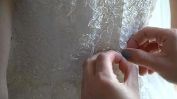 la damigella d'onore abbottona il vestito della sposa
