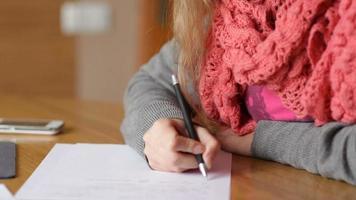 junge Frau, die auf ein Blatt Papier schreibt