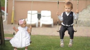 niño y niña en los columpios