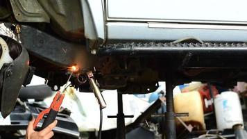 técnico de soldadura de acero de montaje debajo del coche