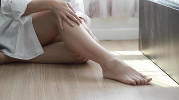 mulher aplicando creme nas pernas