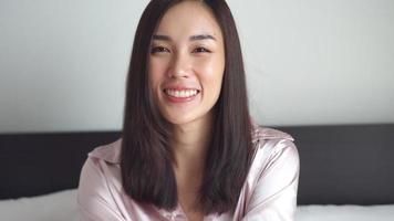 mujer asiática, sonriente, en cama