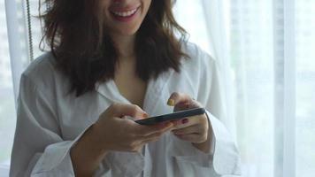 jovem mulher asiática usando telefone celular