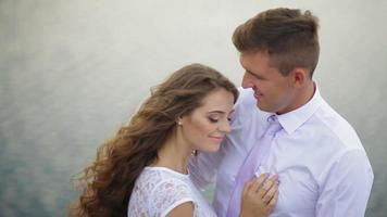 noiva e noivo se abraçando no lago
