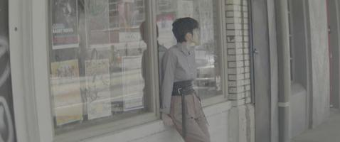 Modelo femenino joven de moda apoyado contra la pared