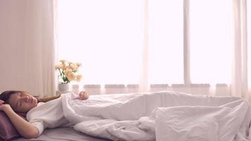 felice bella donna asiatica si sveglia, sorride e allunga le braccia nel suo letto in camera da letto.