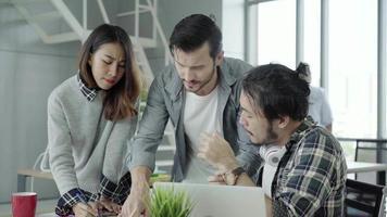 Grupo de gente de negocios vestida informalmente discutiendo ideas en ropa casual elegante trabajando en una computadora portátil.