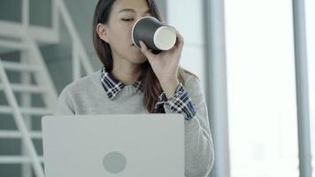 asiatische Geschäftsfrau, die in ihrem Büro über Laptop arbeitet.