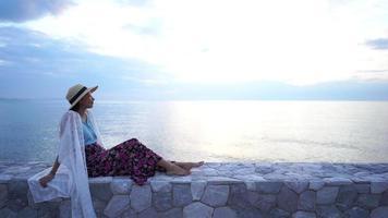mujer joven relajante mirando el océano