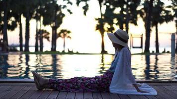 jovem relaxante à beira da piscina