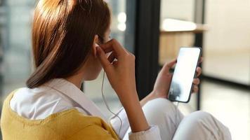 una mujer joven escuchando música en línea desde un teléfono móvil.