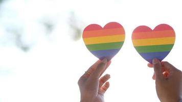 Hands holding rainbow hearts