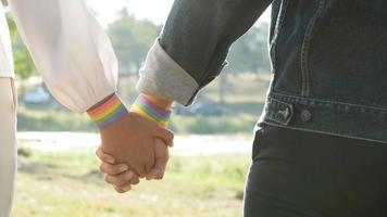 Holding hands with LGBT symbol