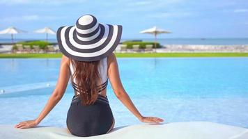 Woman back view by swimming pool