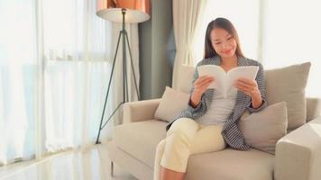 Woman reading book on sofa chair video