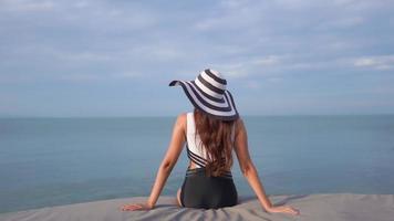 mujer vista trasera sentada junto al mar