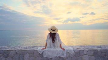 mulher vista traseira admirando o pôr do sol ou nascer do sol