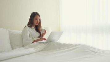 mujer escribiendo en el portátil en la cama