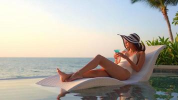 Woman having a drink in lounge chair video