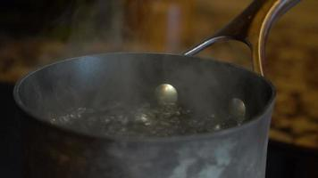 Boiling water on a stovetop in home kitchen video