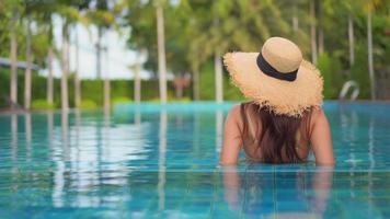 vista traseira de mulher usando chapéu de sol na piscina