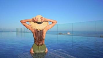 vista posterior de la mujer con sombrero de playa