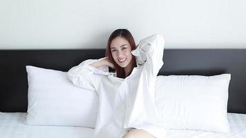 mujer despertando luego estirándose y sonriendo