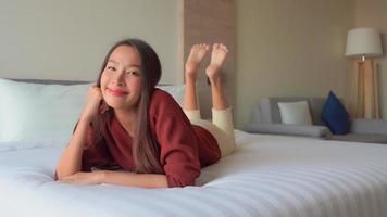 mujer sonriente y relajante en el interior del dormitorio
