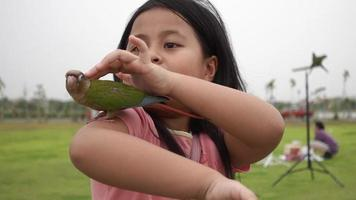A girl holding a parrot