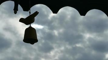 silhueta de um sino contra um céu azul nublado