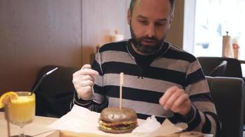 um homem barbudo comendo um hambúrguer video