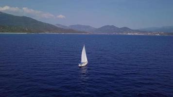 Drone flies towards a yacht in the sea in 4K