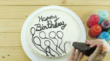 Woman is drawing chocolate on top of birthday butter cake decoration video