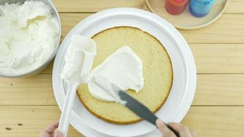Vista hacia abajo de las manos poniendo crema blanca encima del pastel