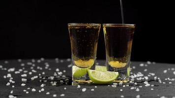 El tequila se vierte en dos vasos sobre fondo negro