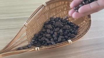 Hand held raw coffee beans tossed into a wooden basket Closeup video slow motion,