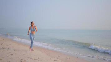 junge asiatische Frau läuft am Strand
