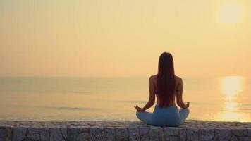 giovane donna meditando di fronte al mare