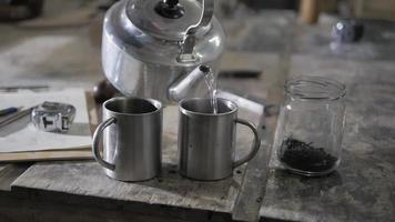 Cerrar la mano vertiendo té en tazas de metal en la mesa de madera