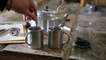Close up hands verser et mélanger le sucre sur des tasses de thé en métal