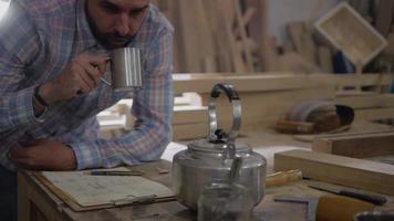 panorâmica de um homem bebendo café ou chá enquanto faz anotações