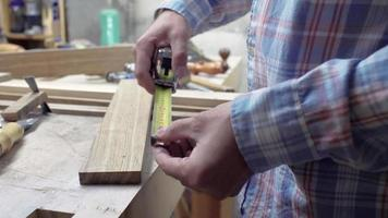 Trabajador realiza medidas de una tabla de madera con cinta métrica