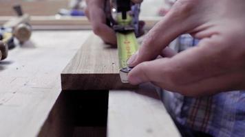 Manos de cerca que miden la longitud del tablero con una cinta métrica de metal. trabajador hace mediciones en una tabla de madera con una cinta métrica. 4k. Vídeo 4k. camara lenta. 24 fps video
