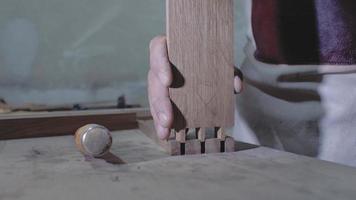 un carpintero une dos piezas de madera hechas con la tecnología de una cola de milano con un martillo. Detalle de un carpintero con juntas de cola de milano. 4k. Vídeo 4k. camara lenta. 24 fps video