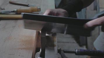 primer plano, un carpintero, serrar una tabla de madera con una sierra de mano