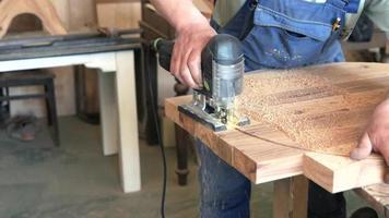 un carpintero corta una mesa redonda con una sierra de calar video