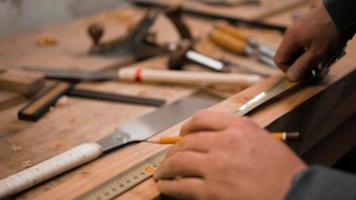 carpintero marca la pieza de trabajo con una cinta métrica y un lápiz
